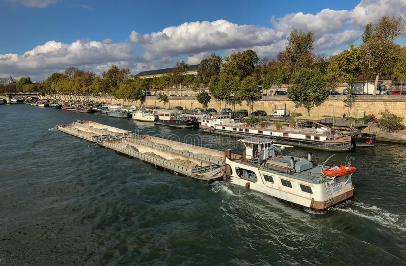 Tugboat pulls long barge down the Seine River in Paris. Oct 2017: A tugboat pulls a double barge down the Seine River, Paris, France, on a sunny afternoon royalty free stock photography