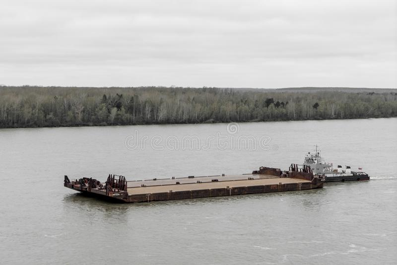 Tugboat pushes barge up the river. Tugboat pushes empty barge without load up the Siberian river royalty free stock photography