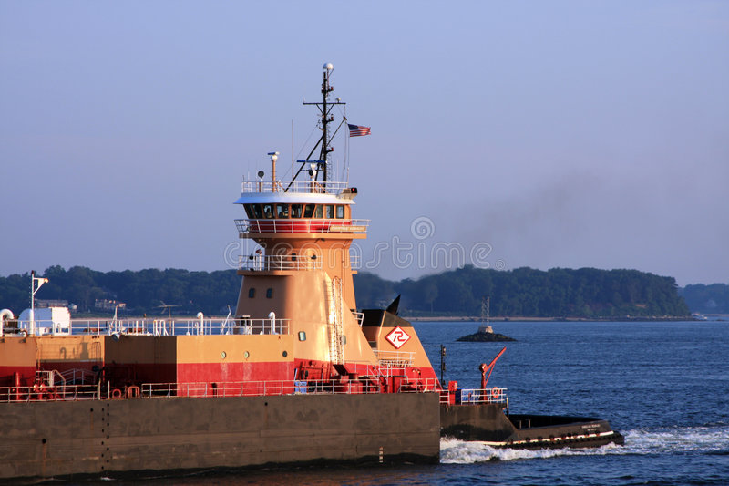 Tugboat pushing barge. Large tugboat pushing a heavy industrial barge royalty free stock images