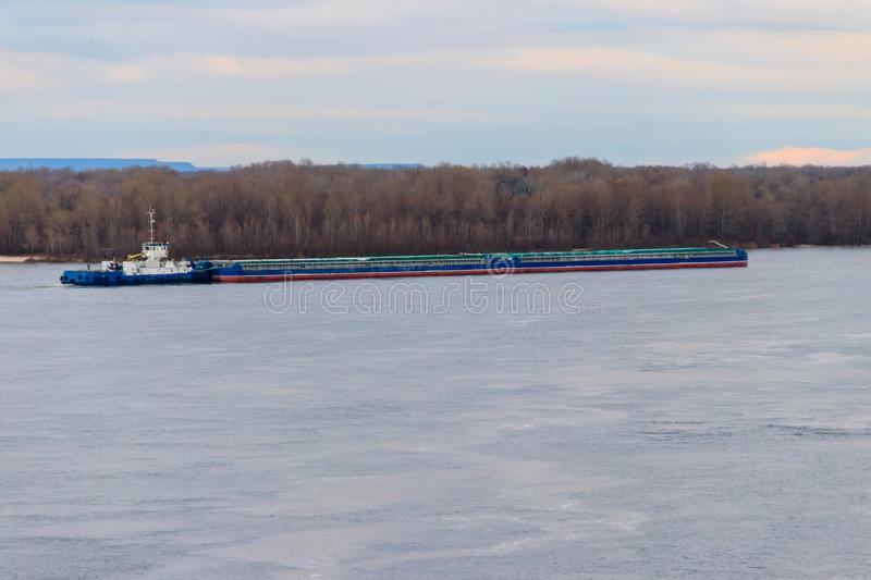 Tugboat pushing a heavy long barge on river Dnieper. Tugboat pushing a heavy long barge on the river Dnieper stock photography