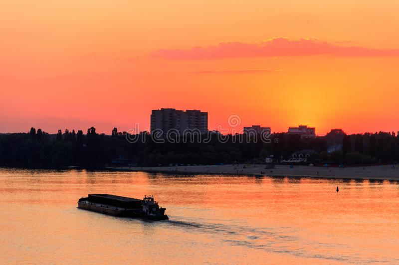 Tugboat pushing heavy long barge on the river Dnieper at sunset. Tugboat pushing a heavy long barge on the river Dnieper at sunset stock photography