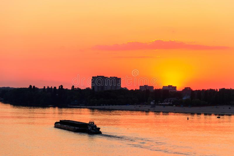 Tugboat pushing heavy long barge on the river Dnieper at sunset. Tugboat pushing a heavy long barge on the river Dnieper at sunset royalty free stock images