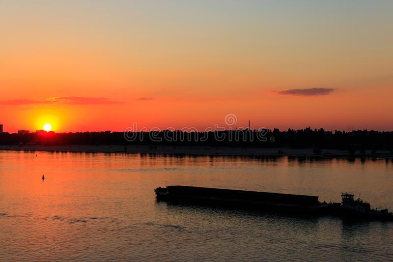 Tugboat pushing a heavy long barge on the river Dnieper at sunset. Tugboat pushing heavy long barge on the river Dnieper at sunset royalty free stock photography