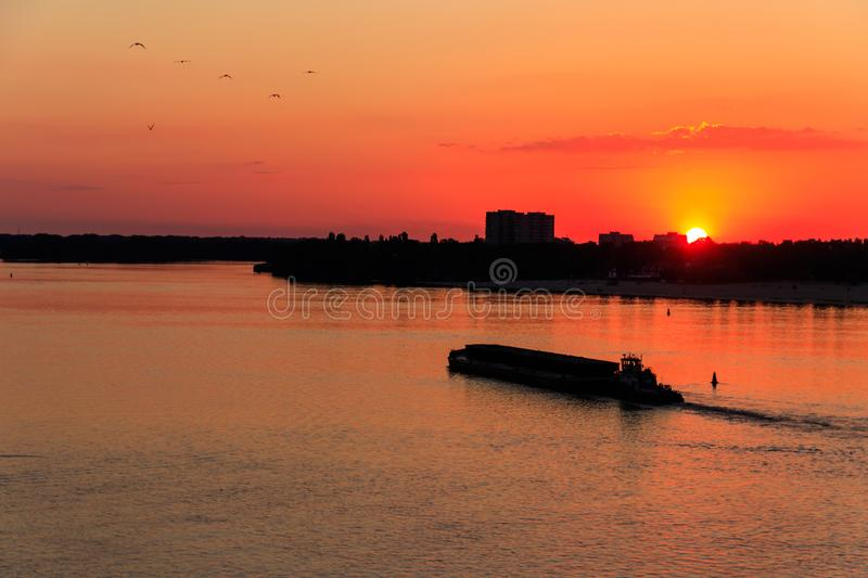 Tugboat pushing a heavy long barge on the river Dnieper at sunset. Tugboat pushing heavy long barge on the river Dnieper at sunset stock images