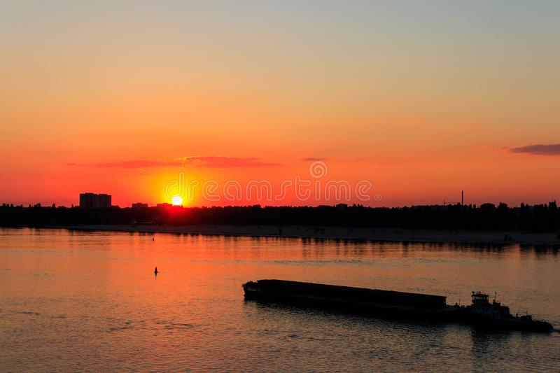 Tugboat pushing a heavy long barge on river Dnieper at sunset. Tugboat pushing a heavy long barge on the river Dnieper at sunset royalty free stock images