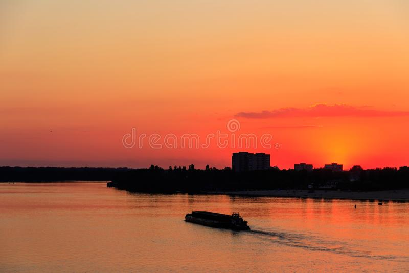 Tugboat pushing a heavy long barge on river Dnieper at sunset. Tugboat pushing a heavy long barge on the river Dnieper at sunset royalty free stock image