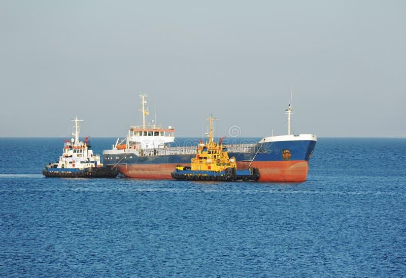 Tugboat que ajuda ao navio de carga da maioria imagem de stock