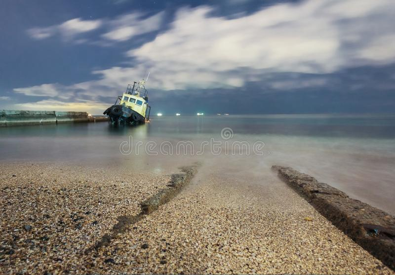 Tugboat ran aground, starry night sky with clouds. stock photo