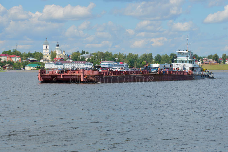 Tugboat `Rechnoy-76` with a barge working as a ferry on the city ferry across the Volga river. MYSHKIN, RUSSIA - JULY 13, 2016: Tugboat `Rechnoy-76` with a barge stock photos