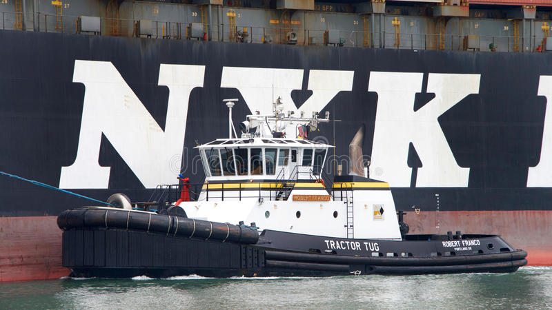 Tugboat ROBERT FRANCO off the port side of NYK APHRODITE. Oakland, CA - August 22, 2016: Tugboats are powerful for their size and strongly built. Tugboat ROBERT royalty free stock photo