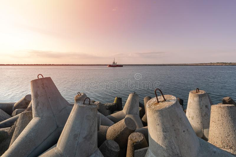 Tugboat sailing in sea to tow ship to port. Tetrapod breakwaters in harbor. Beautiful sunset over the pier stock photos