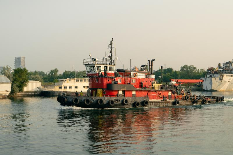 Tugboat sails out from harbor royalty free stock photos