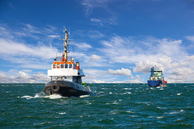 Tugboat at sea. Tugboat and sea bulk carrier with pilot boats stock photo