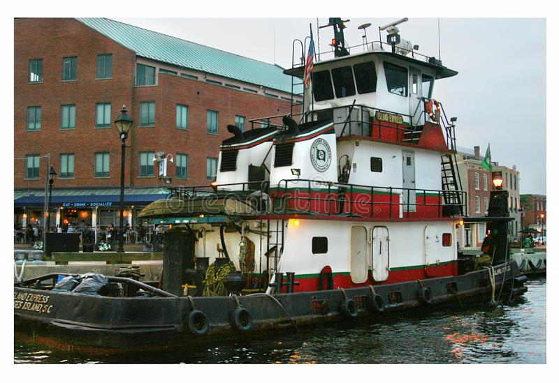 Tugboat in Baltimore harbor. This tugboat sidles up to a pier in Baltimore`s harbor. Tugs are fun to watch as they ply their serious business of guiding huge stock photo