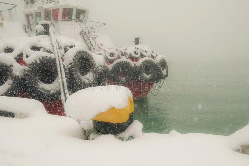 Tugboat. Snow covered tugboat at foggy and snowy seaport stock photo