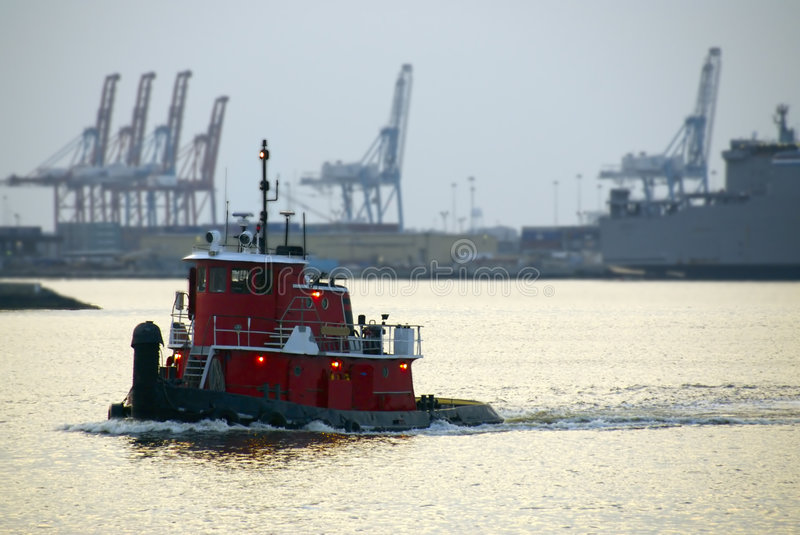 Tugboat at Sunset. A red tugboat cruises the waterways at dusk royalty free stock photo