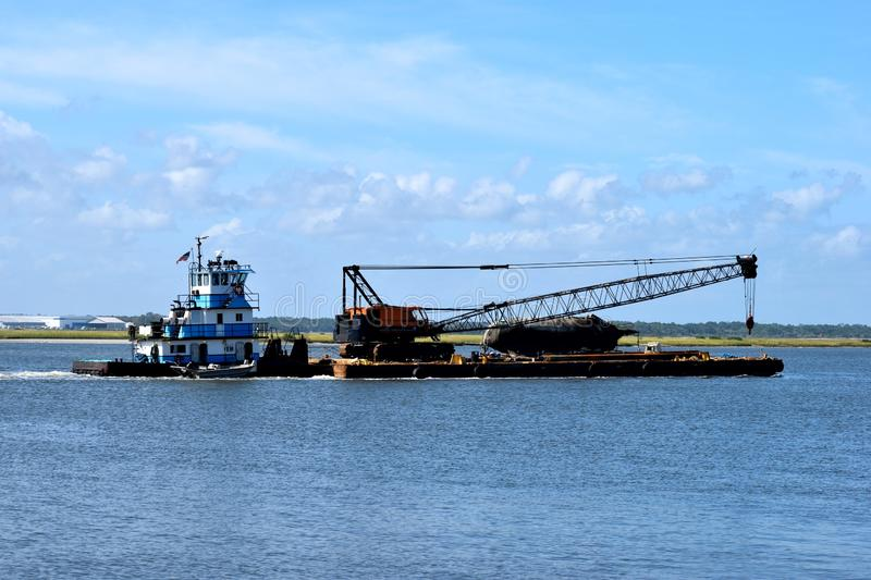 Tugboat towing barge background. Tugboat cruising along the the towing barge with crane St. Augustine. Florida, USA royalty free stock photos