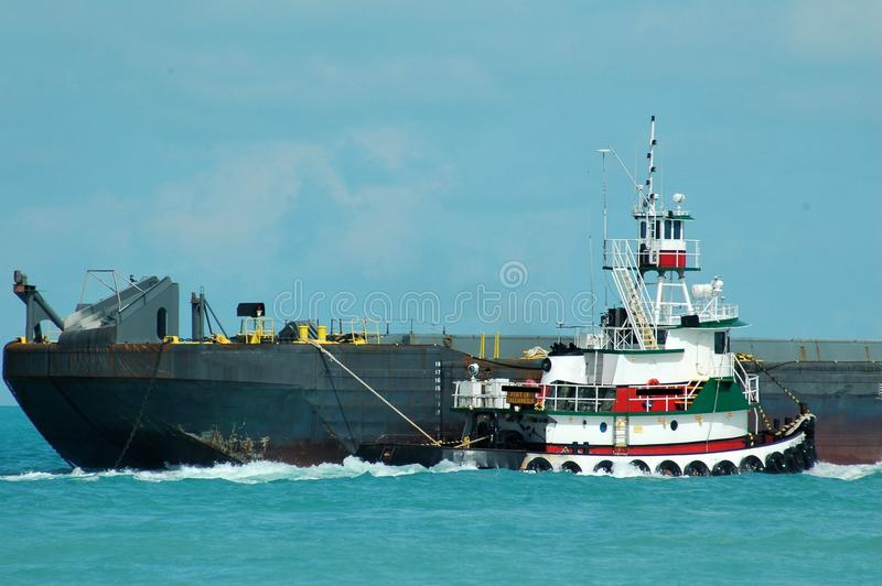 Tugboat towing barge. A tugboat towing a barge near the port royalty free stock photography
