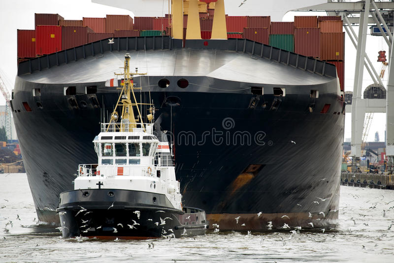 Tugboat towing freighter in harbor. Tugboat towing container ship freighter in harbor royalty free stock photos