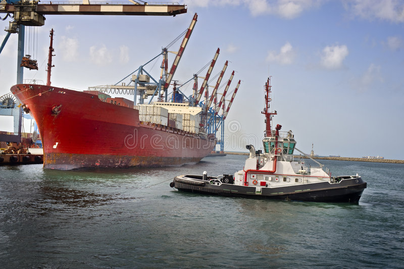 Tugboat at work. Tugboat pulling a cargo ship away from the dock royalty free stock images