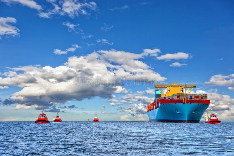 Tugboats and container ship. Tugboat assisting container cargo ship to harbor stock image