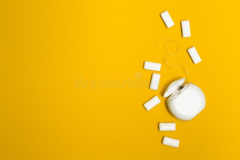 Tuggummi och tandtråd på en gul bakgrund Utrymme för text royaltyfri fotografi