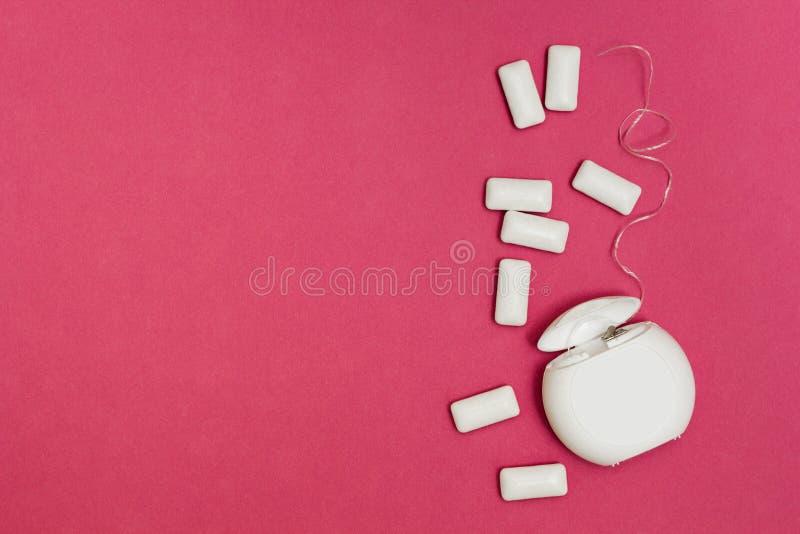 Tuggummi och tandtråd på en rosa bakgrund Utrymme för text royaltyfria foton