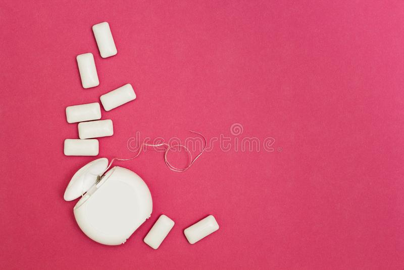 Tuggummi och tandtråd på en rosa bakgrund Utrymme för text arkivfoto