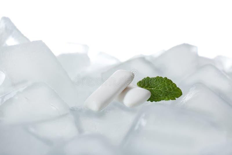 Tuggummin och mintkaramell på iskuber mot vit bakgrund royaltyfri foto