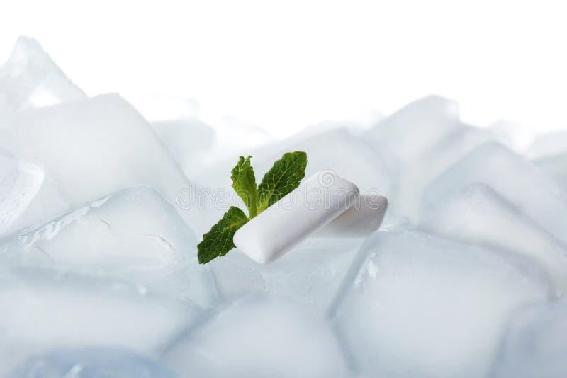 Tuggummin och mintkaramell på iskuber mot vit bakgrund arkivbild