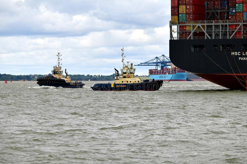 Tugs lead out a container ship from the port from Felixstowe UK. Tugs lead out a container ship from the port The Port of Felixstowe is Britain's biggest stock images