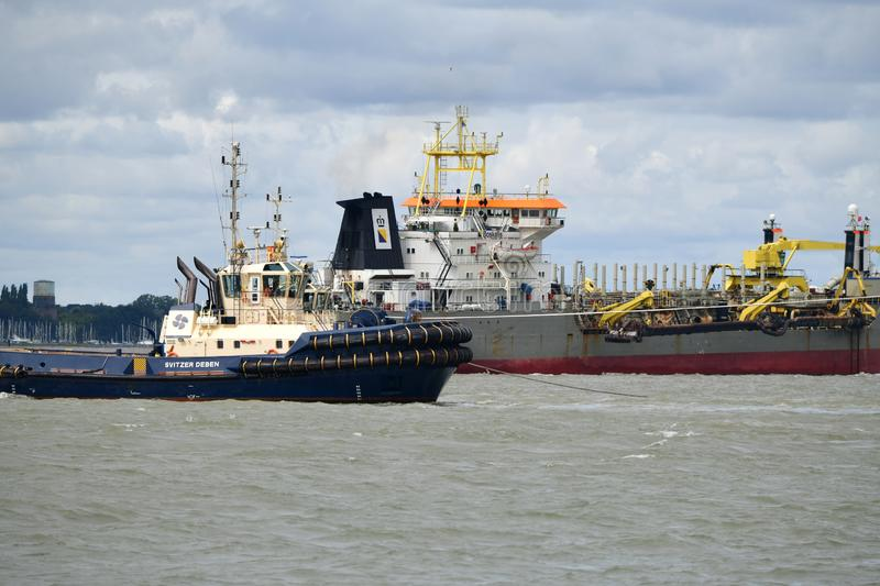 Tugs lead out a container ship from the port from Felixstowe UK. Tugs lead out a container ship from the port The Port of Felixstowe is Britain's biggest stock photography
