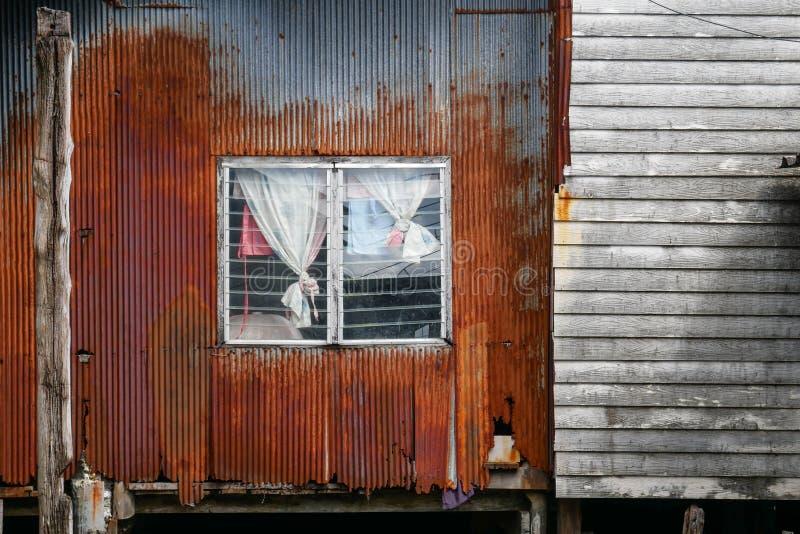 Tugurio arrugginito nell'area di bassifondi in Tailandia, la facciata della casa e facciata con lo strato ondulato arrugginito ed fotografia stock
