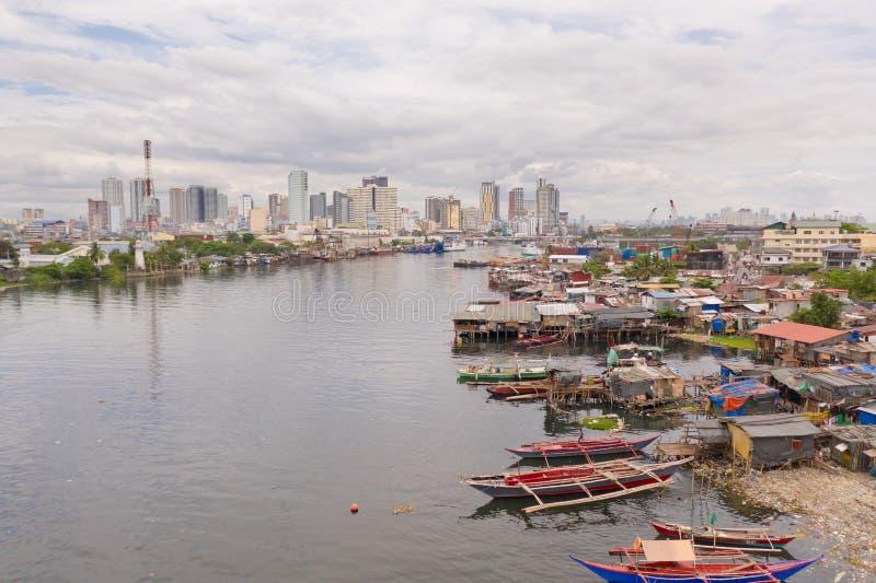 Tugurios de Manila en el fondo de una ciudad grande Casas y barcos de los habitantes pobres de Manila Ponga en contraste los estr imágenes de archivo libres de regalías