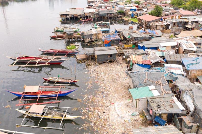 Tugurios y desperdicios en Manila Casas y barcos de los habitantes pobres de Manila Pobres de estancia en las Filipinas imágenes de archivo libres de regalías