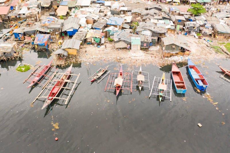 Tugurios y desperdicios en Manila Casas y barcos de los habitantes pobres de Manila Pobres de estancia en las Filipinas imagenes de archivo