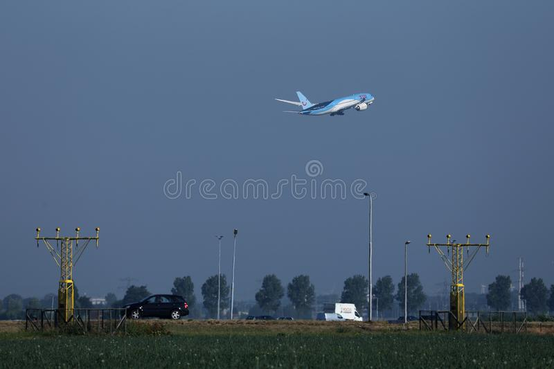 TUI Airways flying up in the sky. TUI Airways airplane flying to vacation destination, branches of tree royalty free stock photo