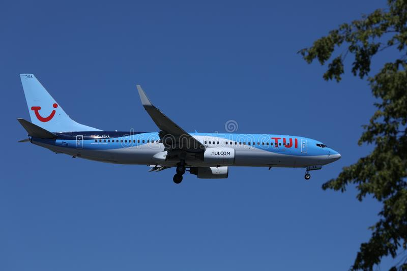 TUI Airways flying up in the sky. TUI Airways airplane flying to vacation destination, branches of tree stock images