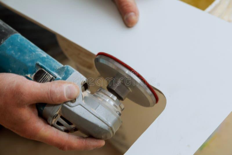 Tuile beige de coupe de travailleur d'homme avec une scie sur un carrelage de coupure photographie stock libre de droits