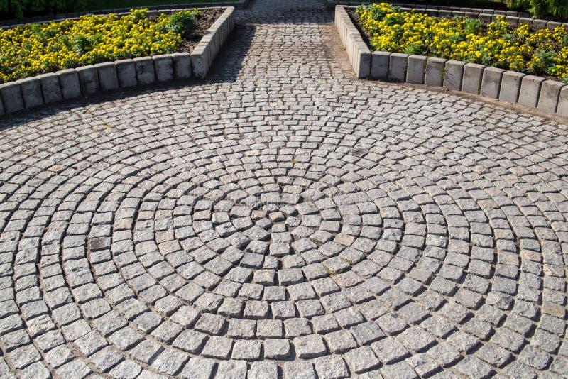 Tuile en pierre et espace vert avec des fleurs en parc de ville photos libres de droits