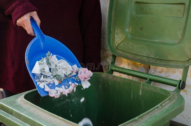 Tuiles cassées de porcelaine sur une pelle à côté de la poubelle - scène de nettoyage image libre de droits