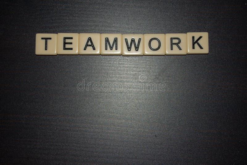 Tuiles de mot de travail d'équipe alignées sur un fond noir Concept Fonctionner ensemble Affaires, éducation, la vie photos libres de droits