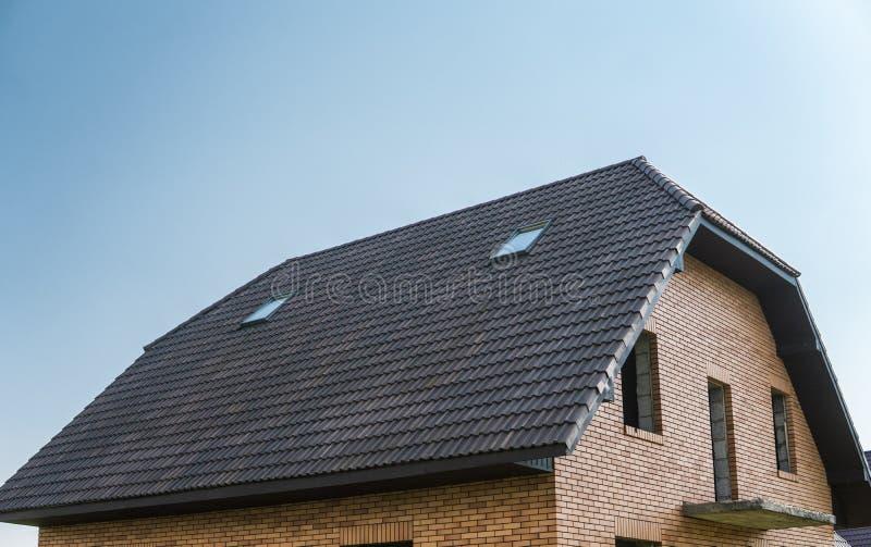 Tuiles de toit brunes naturelles sur un bâtiment contre le ciel bleu images stock