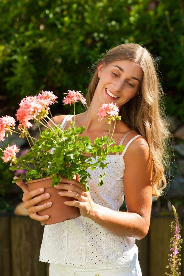 Tuin in de zomerâ gelukkige vrouw met bloemen stock afbeeldingen