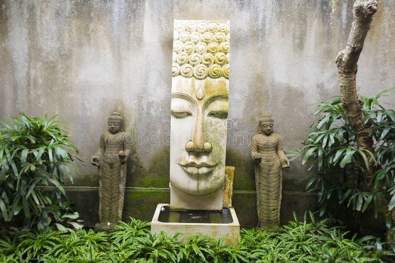 Tuin met Buddah-de eigenschap van het stijlwater en twee kleine standbeelden van stock foto