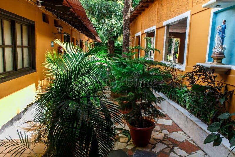 Tuin met installaties en een altaar van een koloniaal huis stock afbeelding