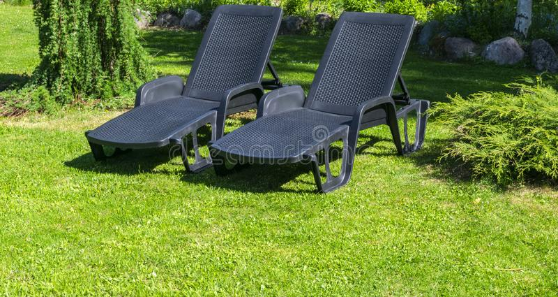 Tuin sunbeds op groen gras Tuinbed voor het zonnebaden en rust de Zomerstoel Strand gestreepte chaise-longues status op groen La royalty-vrije stock foto's