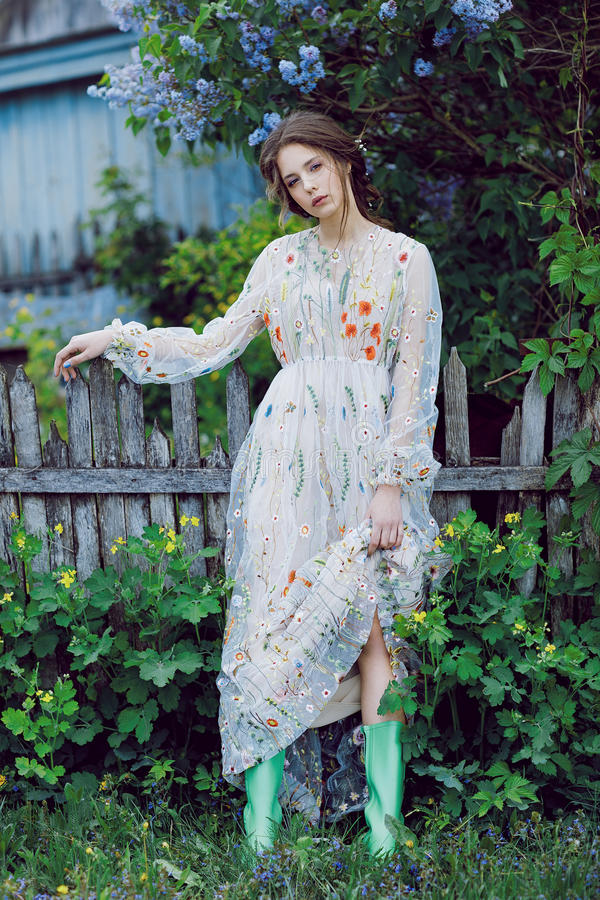 Tuin van Eden Bloemen rond meisje in grijze kleding en groene laarzen Portret van een jong aantrekkelijk meisje in de lange kledi royalty-vrije stock afbeeldingen