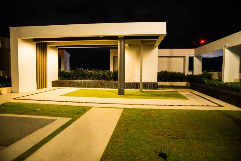 Tuin van modern huis bij nacht stock afbeeldingen