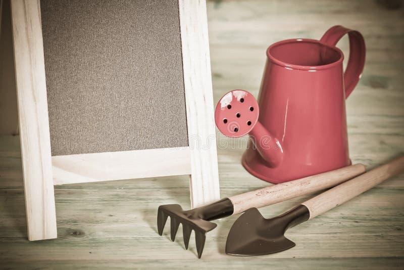 Tuinhulpmiddel en rode gieter stock afbeelding